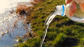 Конец-вверх воды пропуская из пластиковой бутылки, на предпосылке зеленой травы Замедленное движение 1000FPS сток-видео