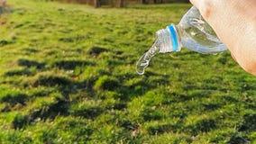Конец-вверх воды пропуская из пластиковой бутылки, на предпосылке зеленой травы Замедленное движение 1000FPS акции видеоматериалы