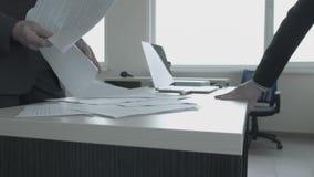 Конец-вверх вождь бросает бумаги на таблице перед девушкой которая остро стоит с ее ногой на таблице акции видеоматериалы