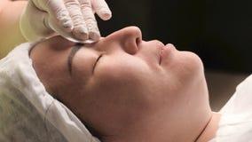 Конец-вверх Восточная женщина лежит на процедуре подмолаживания кожи в салоне красоты медицинского центра Руки beaut стоковое изображение
