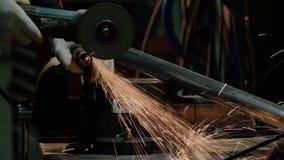 Конец-вверх вращения угловой машины диска во время деятельности Яркие искры от вырезывания металла стоковая фотография rf
