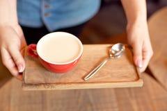 Конец-вверх вручает держать деревянный поднос с чашкой кофе ароматности стоковое фото