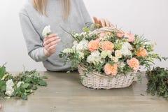 Конец-вверх вручает женскому флористу флористическую мастерскую - женщину делая красивым составом цветка букет в лозе стоковая фотография rf