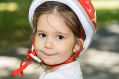 Конец-вверх выразительной маленькой девочки с красочным красным шлемом безопасности Стоковая Фотография RF