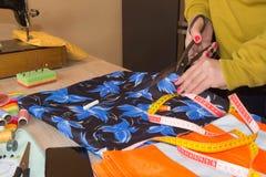 Конец-вверх выстегивать руки ` s женщины шить Женщина портноя работая в его магазине портноя, портняжничая Стоковая Фотография