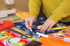 Конец-вверх выстегивать руки ` s женщины шить Женщина портноя работая в его магазине портноя, портняжничая Стоковое Изображение