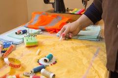 Конец-вверх выстегивать руки ` s женщины шить Женщина портноя работая в его магазине портноя, портняжничая Стоковые Фотографии RF