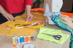 Конец-вверх выстегивать руки ` s женщины шить Женщина портноя работая в его магазине портноя, портняжничая Работа Dressmaker на ш Стоковое фото RF