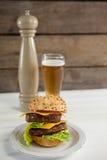 Конец-вверх гамбургера в плите с стеклом пива Стоковые Изображения RF