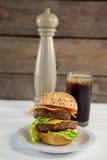 Конец-вверх гамбургера в плите с стеклом холодного напитка Стоковое фото RF
