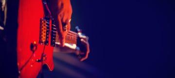 Конец-вверх гитариста играя гитару на этапе Стоковые Изображения