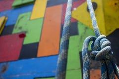 Конец-вверх голубой взбираясь смертной казни через повешение узла перед стеной красочного спортзала взбираясь стоковое фото