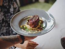Конец-вверх голубой круглой плиты вполне очень вкусного блюда в мужской руке на запачканной предпосылке Кельнер с заказом стоковая фотография