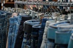 Конец-вверх голубых джинсов на вешалках металла в магазине моды Unisex одежда Концепция для ходя по магазинам дизайна и продаж стоковые изображения