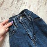 Конец-вверх голубых джинсов на деревянной предпосылке стоковое изображение rf