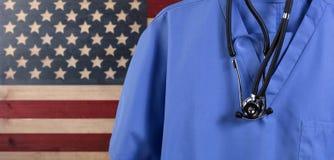 Конец вверх голубая медицинской scrubs и стетоскоп с деревенскими США Стоковые Изображения