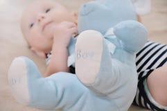 Конец вверх голубой игрушки медведя около newborn ребёнка нося в прокладке Стоковое Фото