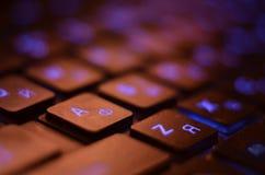 конец вверх Голубые backlight, подсвеченный на компьтер-книжке или компьютере keyborad игры в темноте Клавиатура компьтер-книжки  Стоковые Изображения