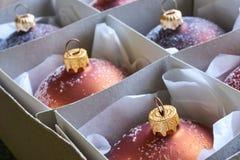 Конец-вверх группы в составе бронза покрасил шарики рождества в картонной коробке Стоковые Фото