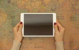 Конец-вверх, девушка держа таблетку на предпосылке карты мира, концепции находить страна для перемещения стоковая фотография