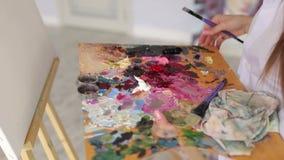 Конец-вверх девушки держа большую палитру красок и щеток для рисовать видеоматериал