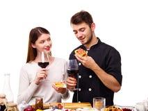 Конец-вверх девушки и парня есть бельгийские waffles, держа стекла вина в их руках Стоковые Изображения RF