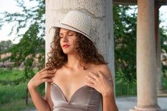 Конец-вверх девушки с шляпой на длинных волнистых коричневых волосах Теплый солнечный свет на заходе солнца стоковые фото