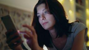 Конец-вверх детенышей сконцентрировал женщину имея наркоманию и инсомнию интернета используя smartphone лежа в кровати дома на сток-видео