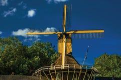 Конец-вверх дома и деревянной желтой ветрянки рядом с каналом на заходе солнца на Weesp Стоковое Изображение