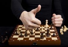 Конец-вверх девушки держа ее руки над деревянной шахматной доской, Стоковое Изображение