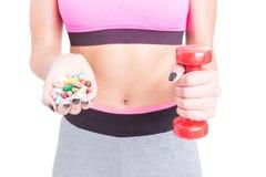 Конец-вверх девушки на спортзале держа пилюльки и гантель Стоковые Изображения RF
