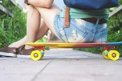 Конец-вверх девушки скейтбордиста сидя на скейтборде внешнем Стоковое Фото
