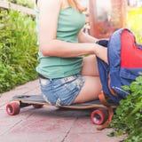 Конец-вверх девушки скейтбордиста сидя на скейтборде внешнем Стоковые Фотографии RF