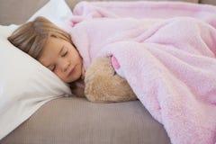 Конец-вверх девушки спать на софе с заполненной игрушкой Стоковое Изображение