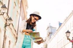 Конец-вверх девушки с мобильным телефоном и город составляют карту Стоковое Изображение