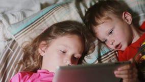 Конец-вверх детей используя планшет пока лежащ на кровати совместно Девушка держа ПК таблетки, шарж мальчика наблюдая видеоматериал