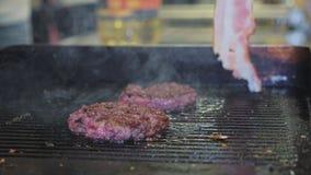 Конец-вверх жаря котлету бургеров на жарить поверхность пока вождь кладет ветчину рядом сток-видео