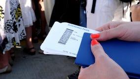 Конец-вверх, женские руки держа билеты посадочного талона авиакомпании, посадочный талон и паспорт в аэропорте видеоматериал