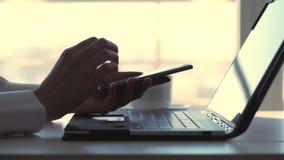 Конец-вверх, женские руки печатая что-то на клавиатуре ноутбука В то же время, бизнес-леди отвечает сообщениям внутри сток-видео