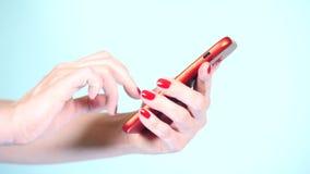 Конец-вверх, женские руки с красным маникюром использует смартфон на покрашенной предпосылке 4k, стрельба замедления видеоматериал