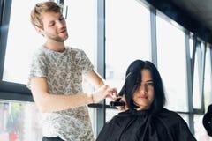 конец вверх Женский парикмахер выправляет коричневые волосы к женщине используя утюг волос в салоне красоты Женский стилизатор де стоковое изображение rf