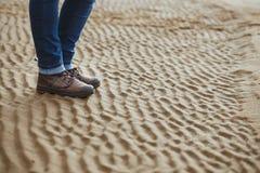 Конец-вверх женских ног в ботинках зимы на влажных пляже, падении или зимнем времени скопируйте космос Стоковое Изображение RF