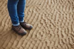 Конец-вверх женских ног в ботинках зимы на влажных пляже, падении или зимнем времени скопируйте космос Стоковое Фото