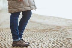 Конец-вверх женских ног в ботинках зимы на влажных пляже, падении или зимнем времени скопируйте космос Стоковая Фотография