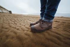 Конец-вверх женских ног в ботинках зимы на влажных пляже, падении или зимнем времени скопируйте космос Стоковое фото RF