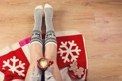 Конец-вверх женских ног в теплых носках с оленем, подарками на рождество, упаковочной бумагой, украшением и чашкой взгляд сверху  Стоковое Изображение