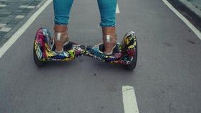Конец-вверх женских ног на ярком и красочном gyroscooter сток-видео
