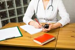 Конец-вверх женских доктора или аптекаря медицины врача сидя на таблице работы, держащ опарник или бутылку пилюлек в руке Стоковые Фото