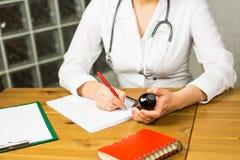 Конец-вверх женских доктора или аптекаря медицины врача сидя на таблице работы, держащ опарник или бутылку пилюлек в руке Стоковое Фото