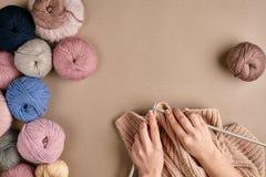 Конец-вверх женских рук вязать цвет бежа свитера или шотландки шерстей Взгляд сверху Стоковое Фото